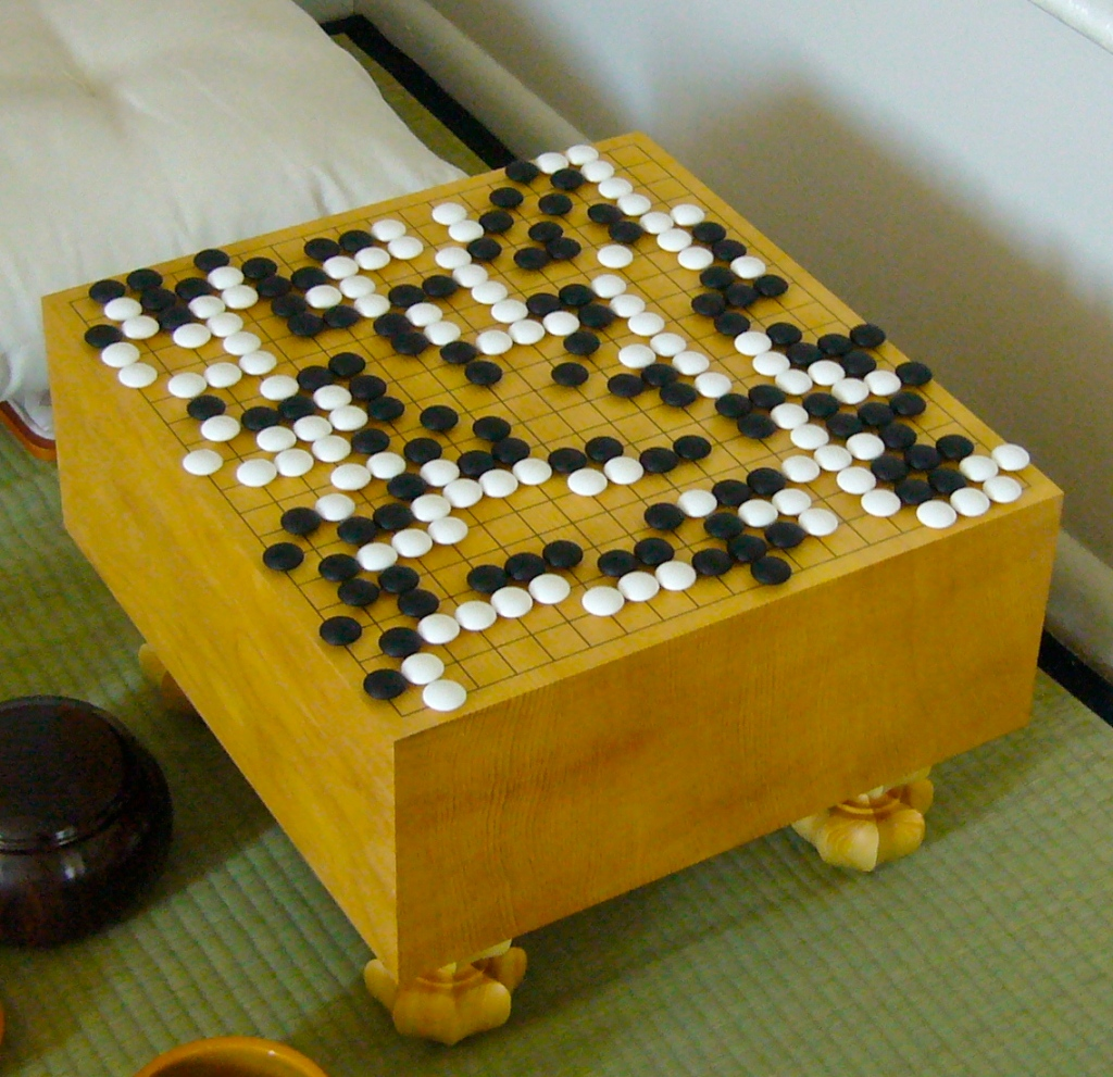A wooden Go board mid game.
