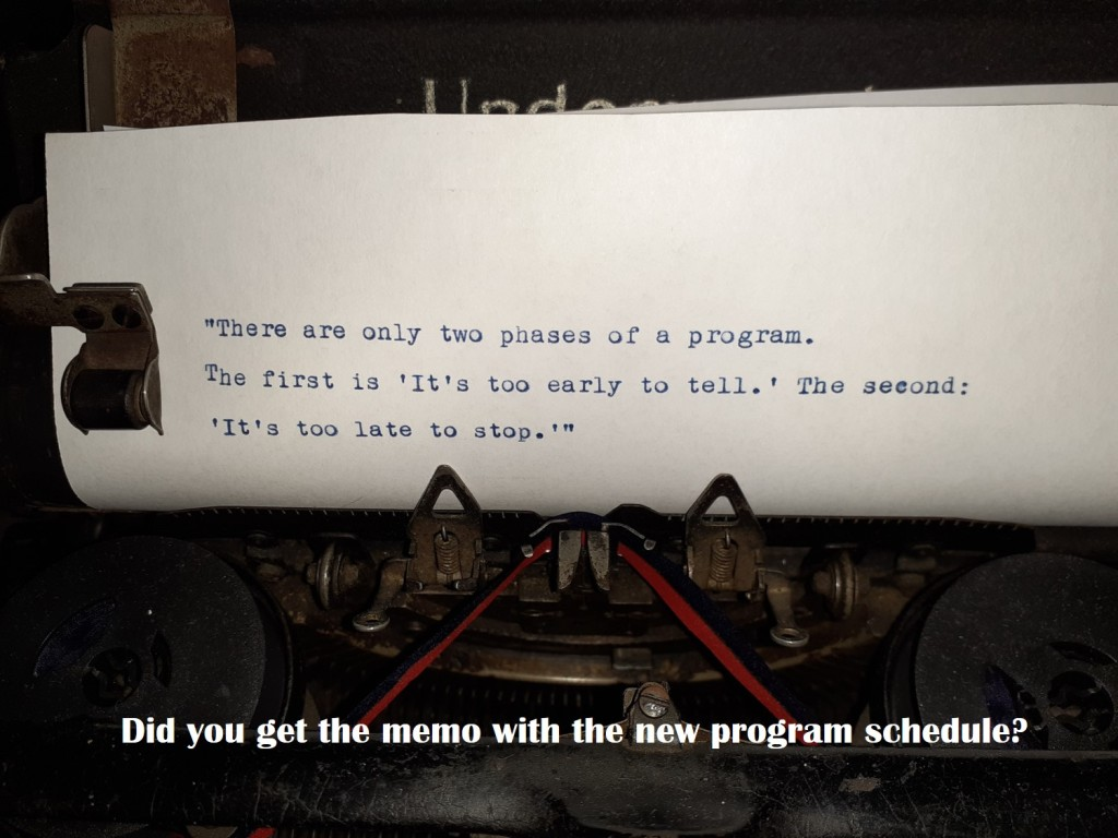 """A paper in a typewriter. The text on the paper says """"There are only two phases of a program. The first is 'It's too early to tell.' The second 'It's too late to stop.'"""" Below the image there is a subtext that says: Did you get the memo about the program schedule update?"""