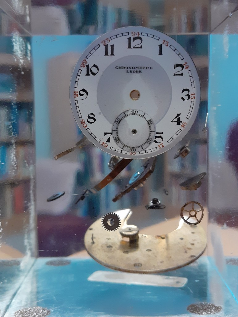 """A picture of an acrylic paperweight suspending parts of a watch. The caption reads """"Thinking in terms of parts was fine, for a time."""" Credit: Edgar Zapata, zapatatalksnasa.com"""